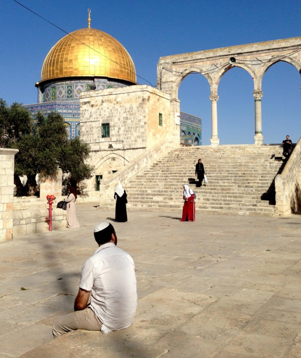 Tamir Mizrachi, who is sitting with his back to the camera, visits Jerusalem's Temple Mount / Noble Sanctuary, a place holy to Jews and Muslims. Israel allows Jews like Mizrachi to visit, but they are not allowed to pray at the hilltop site. Jews pray below at the nearby Western Wall.