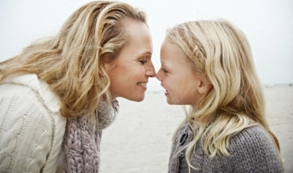 Mother and daughter touching noses --- Image by © Oliver Rossi/Corbis