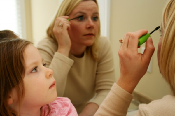 A girl watches her mother putting on makeup
