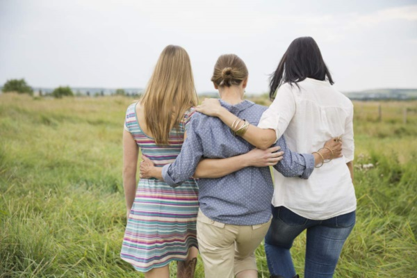 Rear view of female family members walking through field