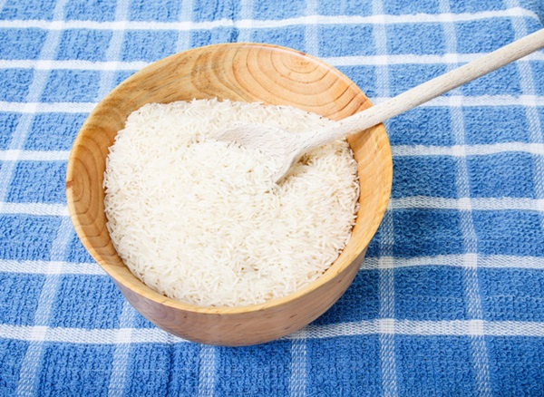 White rice with wood spoon in wood bowl